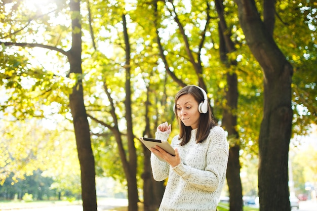 Красивая счастливая жизнерадостная шатенка в белом свитере с планшетом, слушающая музыку в белых наушниках в осеннем парке в теплый день. осень в городе.