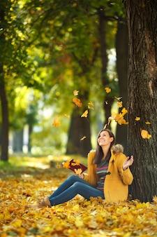 Красивая счастливая улыбающаяся шатенка в желтом пальто и джинсах сидит под кленом с красной книгой в осеннем городском парке в теплый день. осенние золотые листья. концепция чтения