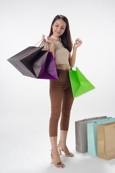 Красивая дама, держащая хозяйственные сумки в руке, со счастливым чувством, шопоголик, модель позирует