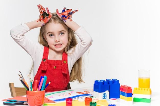 Красивая маленькая девочка с руками в краске