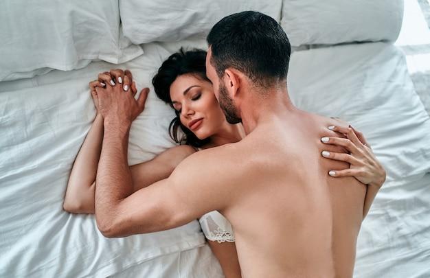 ベッドでセックスをしている下着の美しい男と女