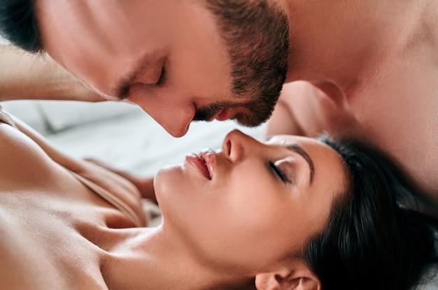 ベッドでキスする下着の美しい男と女