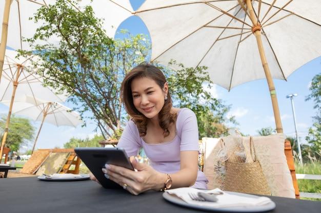 Красивая женщина средних лет сидит в продуктовом магазине и работает с планшетным компьютером