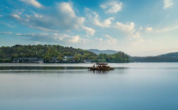 Красивые природные пейзажи и деревянные лодки западного озера в ханчжоу