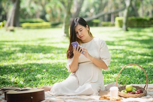 Красивая беременная женщина на пикнике и с помощью мобильного телефона в саду