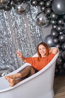 Красивая рыжеволосая девушка радуется сидению одетой в ванну. на фоне мишуры и воздушных шаров. концепция успеха.