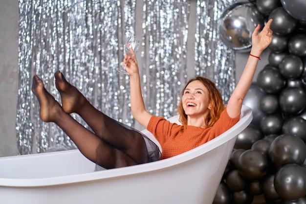 美しい赤毛の少女はお風呂に身を包んで座って喜ぶ