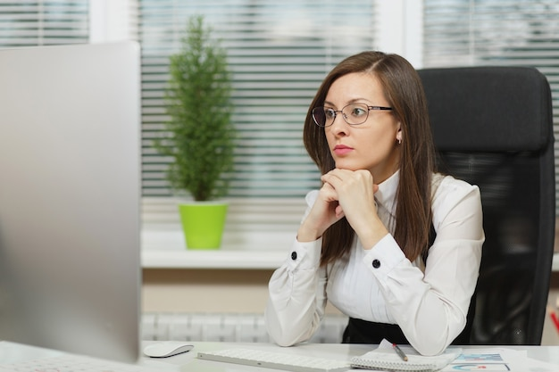 정장을 입고 안경을 쓰고 책상에 앉아 있는 아름다운 진지하고 몰두한 갈색 머리 비즈니스 여성, 밝은 사무실에 있는 문서가 있는 현대적인 모니터로 컴퓨터 작업, 옆을 바라보는