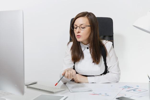 정장을 입고 안경을 쓰고 책상에 앉아 있는 아름답고 진지하고 몰두한 갈색 머리 비즈니스 여성, 밝은 사무실에서 문서가 있는 현대적인 모니터로 컴퓨터 작업,