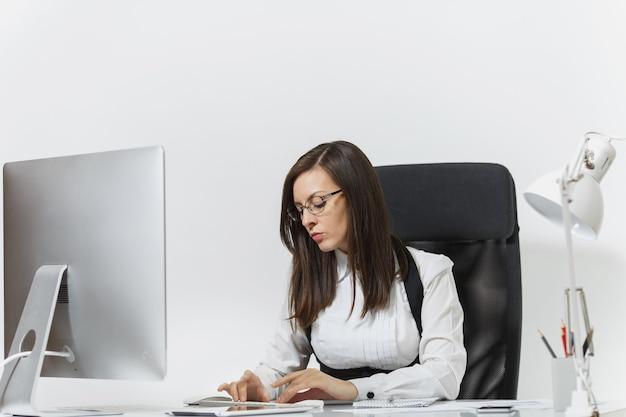 Красивая серьезная и увлеченная каштановая бизнес-леди в костюме и очках сидит за столом, работает за компьютером с современным монитором с документами в светлом офисе.