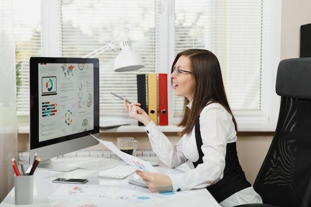 미소 짓는 아름다운 갈색 머리 비즈니스 여성은 양복과 안경을 쓰고 책상에 앉아 커피 한 잔을 들고 가벼운 사무실에서 문서로 컴퓨터 작업을 하고 모니터를 보고 가리키고 있습니다