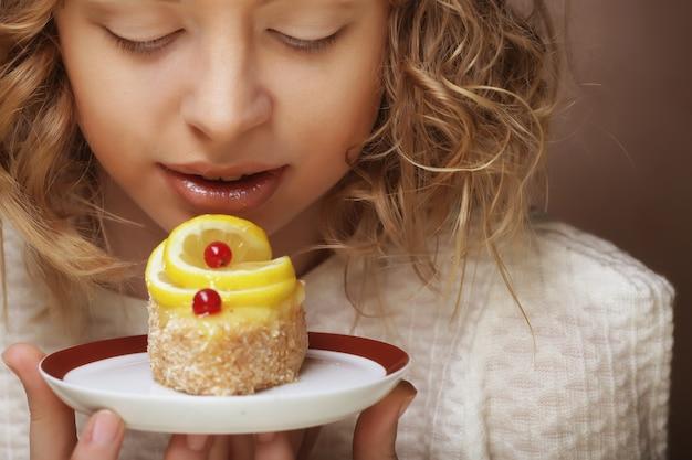 ケーキと美しい笑顔の若い女性