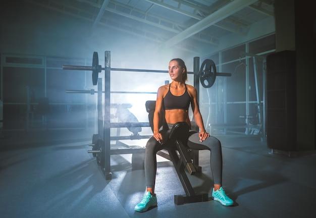 Красивая спортсменка сидит в фитнес-клубе