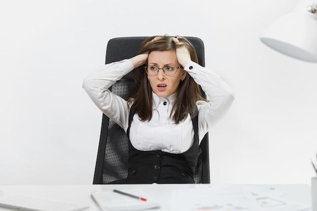 아름다운 피곤하고 당황하고 스트레스를 받는 갈색 머리 비즈니스 여성이 양복과 안경을 쓰고 책상에 앉아 가벼운 사무실에서 문서를 가지고 현대 컴퓨터에서 일하고 있습니다.