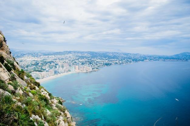 Прекрасный вид со знаменитой скалы пенон-де-ифач на побережье коста бланка на берег города кальпе, испания.