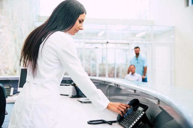 Красивая женщина-врач принимает входящий звонок на приемной современной больницы