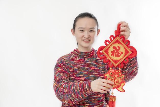 У красивой женщины в руке китайский узелок с счастливыми иероглифами.