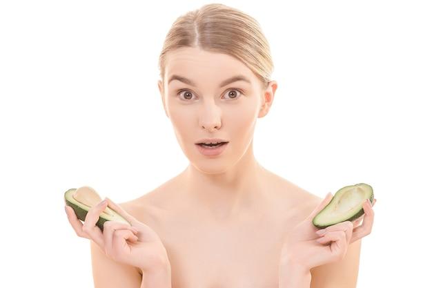 Красивая женщина, держащая две половинки авокадо на белом фоне