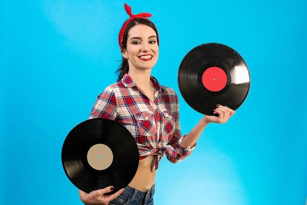 青い背景にビニールレコードを保持している美しい女性
