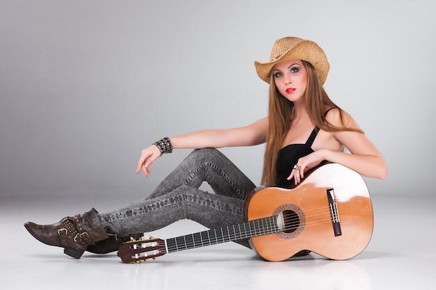 カウボーイハットとアコースティックギターの美しい女性。