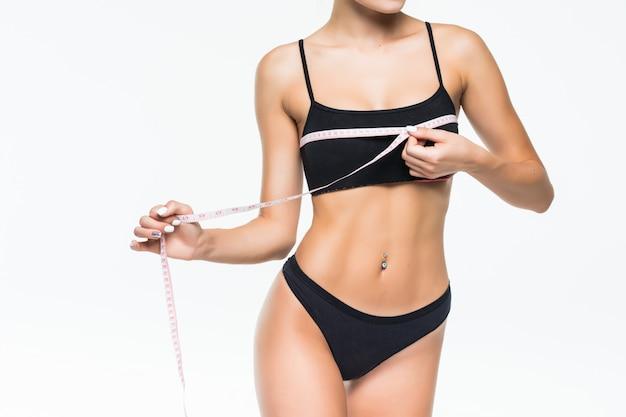 美しい女性は青い測定器で黒のランジェリーでウエスト数を測定します。細い腰、細長い脚。スポーツ、ダイエット、体重減少。