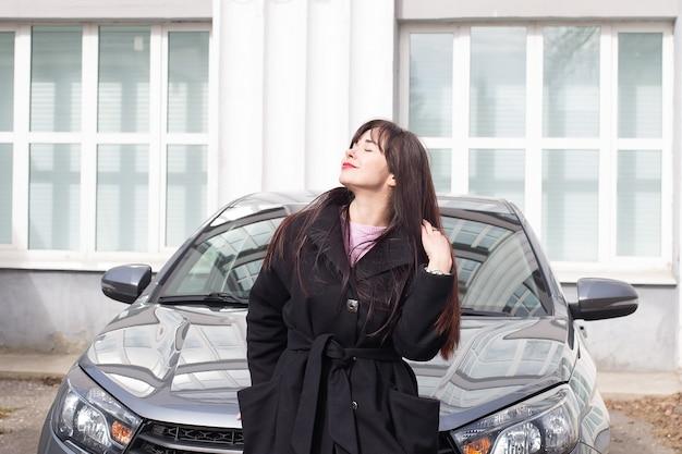 Красивая женщина на улице рядом с машиной