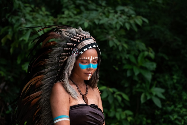 鳥の頭飾りの羽を身に着けている美しい女性。茶色の色でボディをペイントし、青い色の顔で、森でポーズをとるモデル