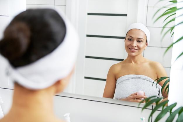 Красивая женщина с дезодорантом в руках стоит перед зеркалом в ванной