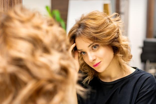 Красивая молодая кавказская женщина смотрит на свое отражение в зеркале, проверяя прическу