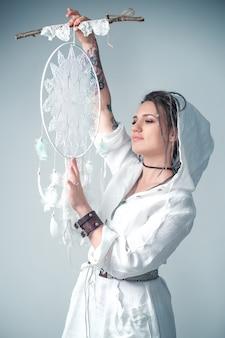 Красивая молодая девушка с дредами в стиле бохо держит в руках ловец снов. медитация и релаксация