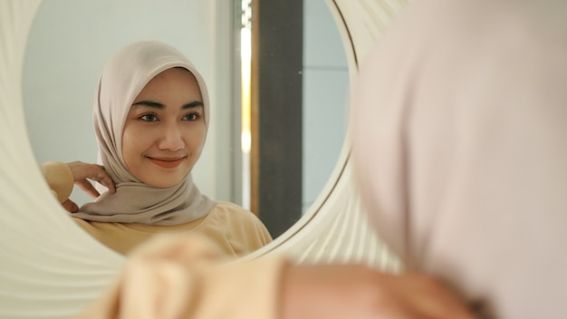 美しい若いイスラム教徒は鏡の中で優しく微笑む