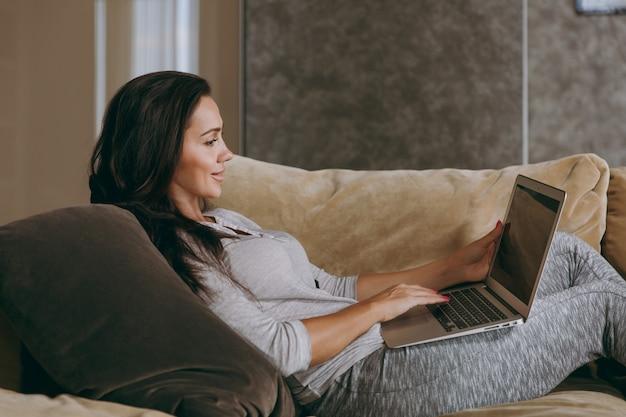 自宅でソファに横になり、リビングルームでリラックスし、ラップトップで作業している美しい若い女性
