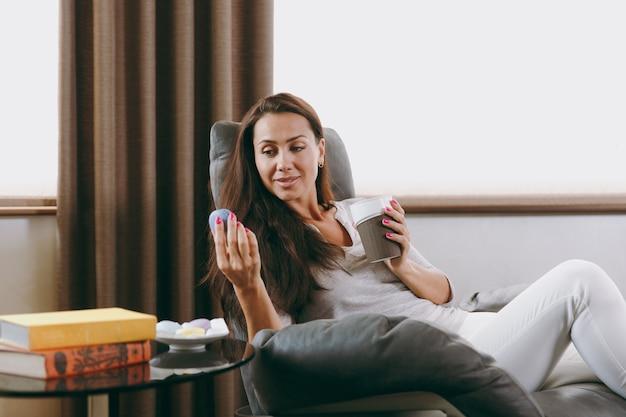 집에서 아름 다운 젊은 여자는 창 앞의 현대 의자에 앉아 그녀의 거실에서 휴식을 취하고 커피 또는 차를 마시는