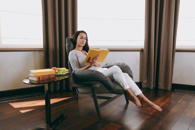집에서 아름 다운 젊은 여자는 창 앞의 현대 의자에 앉아 그녀의 거실에서 휴식을 취하고 책을 읽고