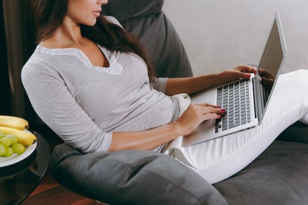 집에서 아름다운 젊은 여자가 창 앞의 현대 의자에 앉아 그녀의 거실에서 휴식을 취하고 노트북으로 작업
