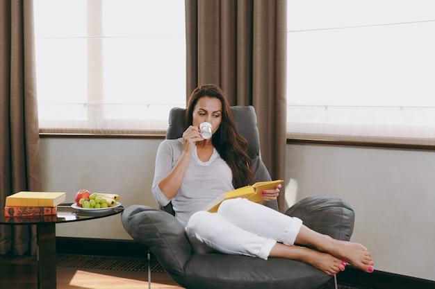 집에서 아름다운 젊은 여성이 창 앞의 현대 의자에 앉아 그녀의 거실에서 휴식을 취하고 책을 읽고 커피 또는 차를 마시는