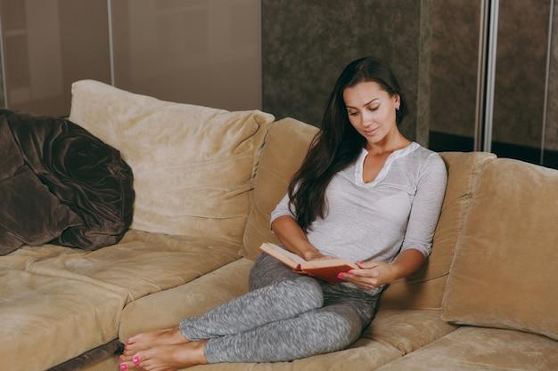 집에서 아름다운 젊은 여자가 소파에 앉아 그녀의 거실에서 휴식을 취하고 책을 읽고