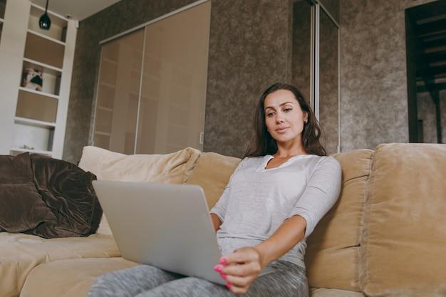 집에서 아름다운 젊은 여자가 소파에 앉아 그녀의 거실에서 휴식을 취하고 노트북으로 작업