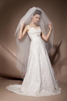 웨딩 드레스를 입고 포즈를 취하는 아름다운 젊은 여성