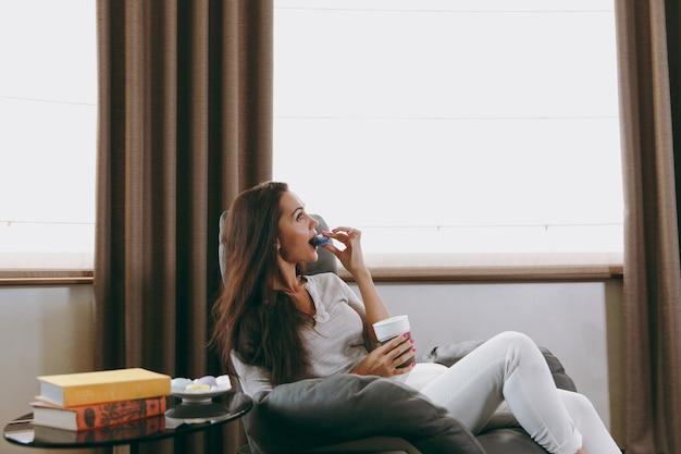 Красивая молодая женщина сидит на современном стуле перед окном дома, ест миндальное печенье и пьет кофе или чай