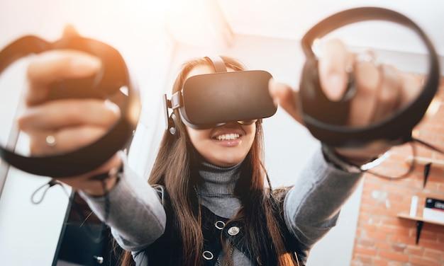 Красивая девушка играет в игры с очками виртуальной реальности