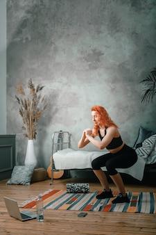 美女は家でスポーツに出かける。スクワットをし、ラップトップで時計、寝室でブログを撮影している赤い髪の陽気なスポーティな女性
