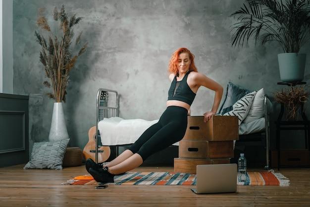 美女は家でスポーツに出かける。赤い髪の陽気なスポーティな女性は上腕二頭筋を振る、ノートパソコンでボックスや時計を腕立て伏せし、寝室でブログを撮影する