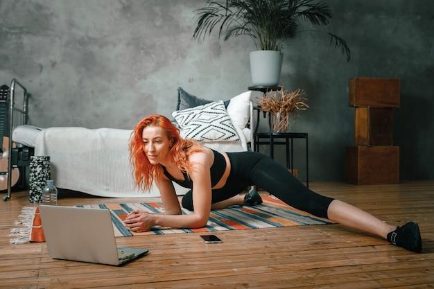 美女は家でスポーツに出かける。赤い髪の陽気なスポーティな女性が脚に伸びてノートパソコンで見て、寝室でブログを撮影