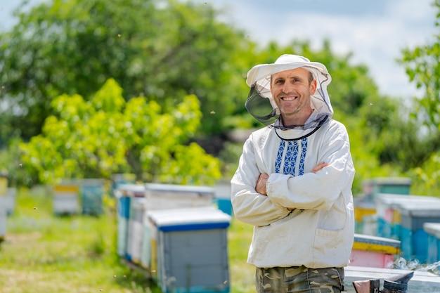 Пчеловод стоит крестиком возле пасеки. пчеловодство. пасека.