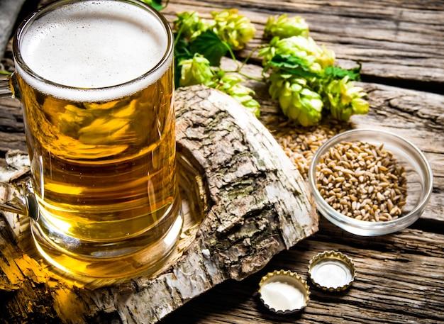 ビールスタイル。白樺のスタンドにビールのグラス、木製の背景にモルトとホップ。