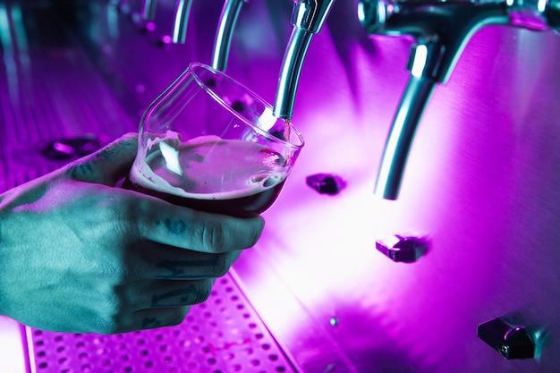 ビールはパブでタップします。誰でもない。セレクティブフォーカス。アルコールの概念。ビンテージ・スタイル。ビールクラフト。バーテーブル。鋼の蛇口。光沢のある蛇口。ビールのグラス。オクトーバーフェストのコンセプト