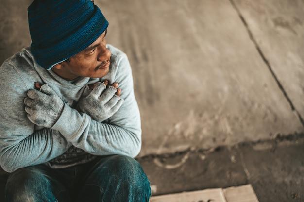 乞食たちは橋の下にホームレスのメッセージを添えて座っています。助けてください。