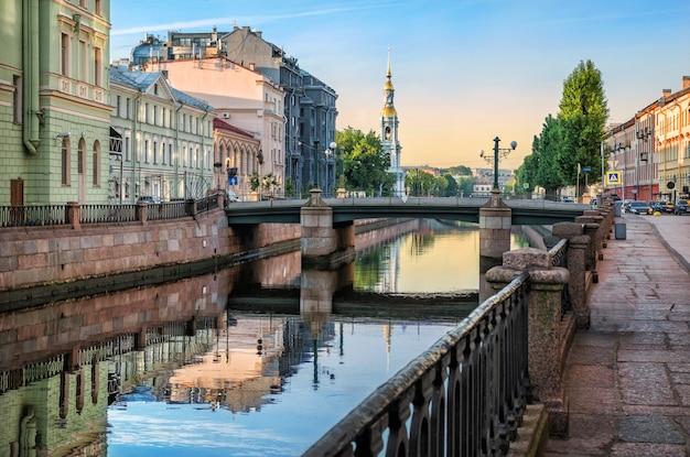 Колокольня никольского собора в санкт-петербурге и дома на крюковом канале у торгового моста ранним летним солнечным утром.