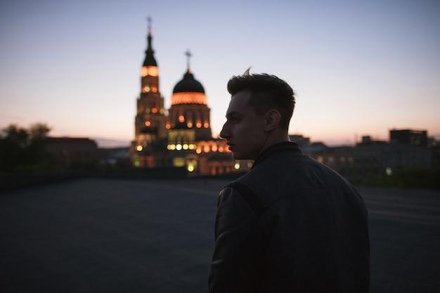 신자는 기독교 교회에갑니다. 밤하늘의 배경과 예배의 빛나는 장소에 대해 젊은 남자의 실루엣
